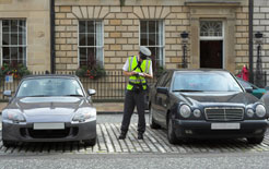 A civil enforcement officer - formerly a parking attendant - issues a parking ticket