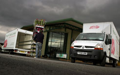 Worker unloads flowers from Renault van