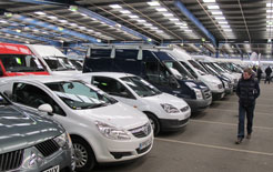 A buyer inspects a line up of used vans for offer at BCA auction