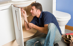 A plumber working on a sink. HMRC is targeting plumbing trades for non-payment of tax