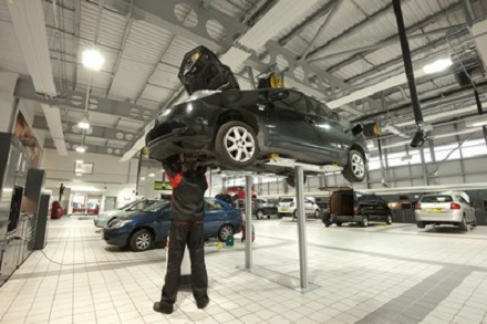 Service department at Toyota dealership with car up on ramp