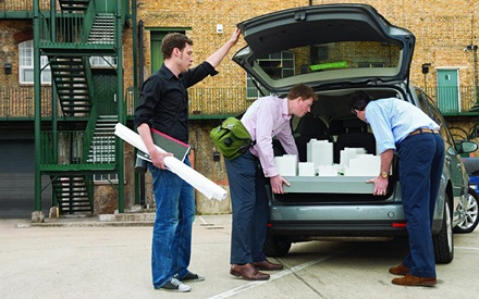 Architects load an architectural model into a car