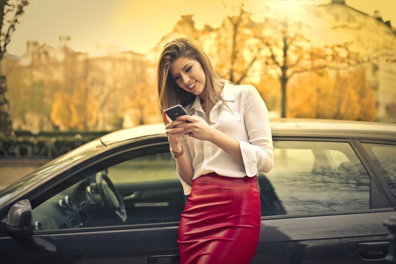 Businesswoman on her smart phone with car