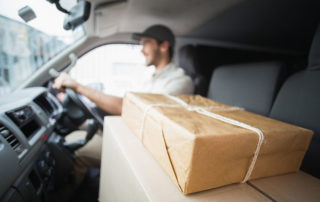 delivery driver driving van with parcels on seat o pk8akbr